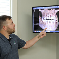 Dr. Renz examining an image of a patient's teeth